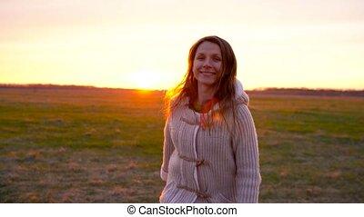 Woman running through a wide field at sunset