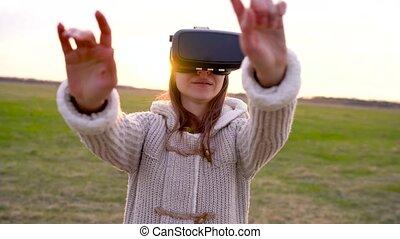 Girl uses a virtual reality glasses outdoors