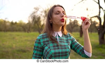 Woman blowing soap bubbles outdoors - slow motion - Happy...