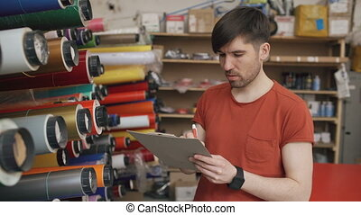 Young worker in warehouse with clipboard checking inventory....