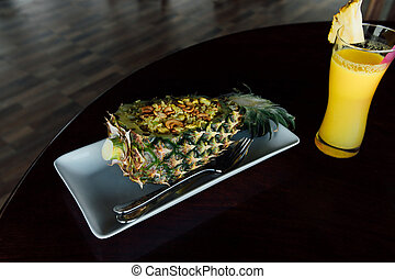 Fried rice inside pineapple next to a glass of juice with a...