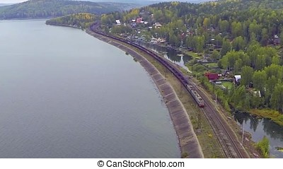 Aerial view on freight train goes through the bridge. train or freight train goes on rails view from sky. View on freight train rides on the tracks near forest. Railway wagons. Transportation, railroad