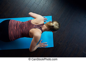 Fit young woman doing press-ups as she works out on a mat at...