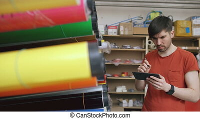 Young worker in warehouse with tablet computer checking...