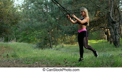 A girl with a sporty physique in sportswear makes fitness...