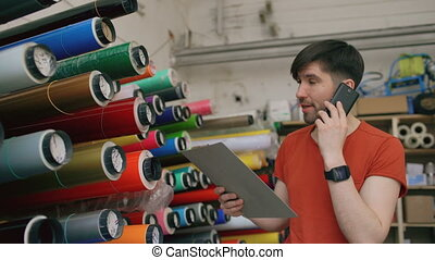 Young worker in warehouse talking smartphone and checking...