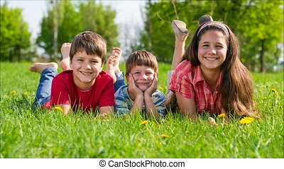 Three kids lying together on green grass meadow