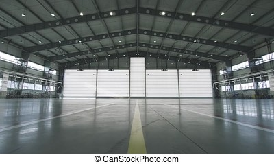 Roller shutter door and concrete floor inside factory building for industrial background. Airplane in front of half opened door to hangar. The open door of the hangar. Mechanic opening the door