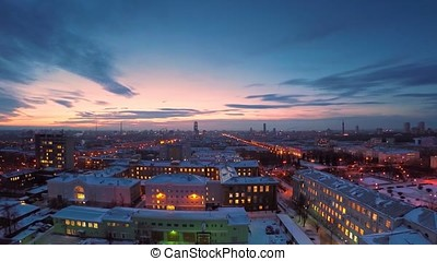 Evening city in winter timelapse. Evening city in winter view from roof timelapse. Panoramic view on the town and roofs under the snow, timelapse. Street night city lights