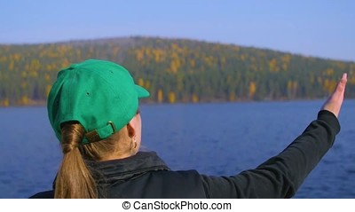 The girl shows the lake, forest in summer day. the girl...