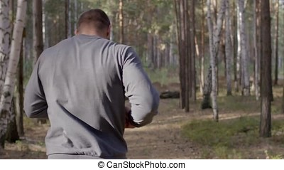 Male runner running along a nature trail through the woods...