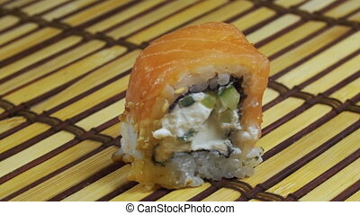 One Sushi Roll on a Bamboo Mat Rotates