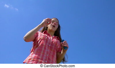 Girl blowing up the soap bubbles against blue sky, slow motion