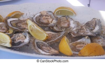 Mussels in a plate with lemons in restaurant. - Mussels in a...