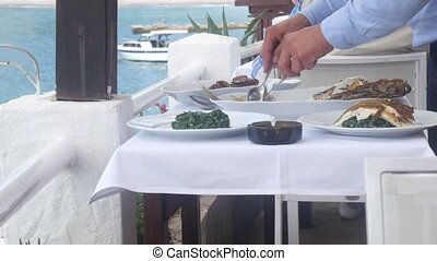 The waiter is cutting fish in the restaurant on table - The...