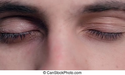 Closeup of young man's blue eyes with problematic skin acne...