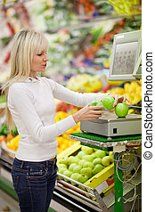 Beautiful young woman shopping for fruits and vegetables in...