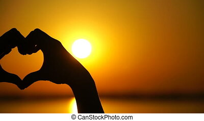Woman makes heart and hands directs the sunset.