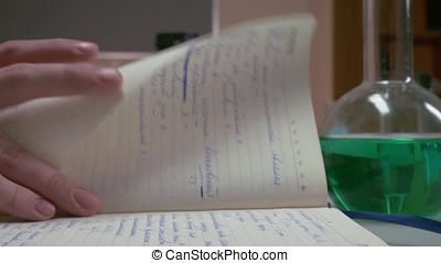 Hands open and looking something in a diary, notebook. hands of the scientist writing on notebook, women's hands, making the entry in the diary. hands and opened vintage book over table.