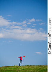 joyful young woman jumping cheerfully in the midlle of a green f