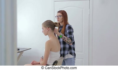 Professional hairdresser doing hairstyle for teen girl -...