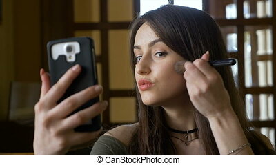 Beautiful teen retouching make up with her smart phone using a brush to apply blush on her cheeks