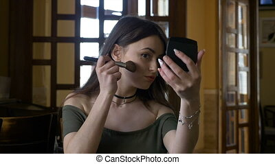 Young attractive woman retouching her makeup at the restaurant before meeting