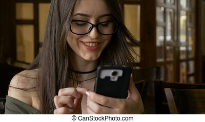 Joyful smiling woman having her coffee and scrolling on her smart phone
