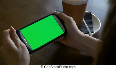 Woman watching a smart phone with chroma key green screen in landscape mode in a coffee shop