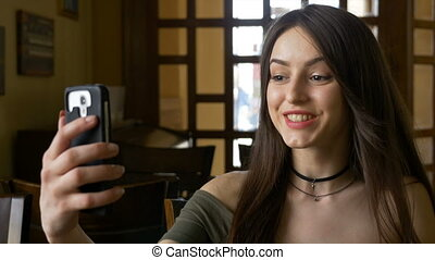 Young woman having a video call from coffee shop