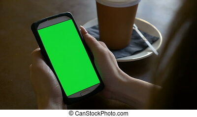 Closeup hands of woman holding smart phone with chroma key green screen in a cafe