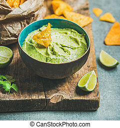 Fresh guacamole sauce in blue bowl and chips, square crop -...