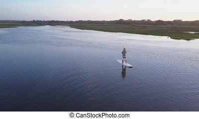 Man stand up paddleboarding - Aerial view of man stand up...
