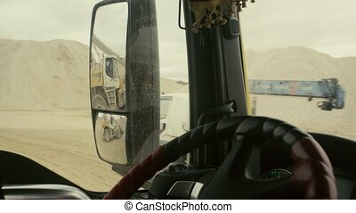 View in truck's rearview mirror on work in quarry