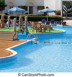 Sun chairs and umbrellas near hotel swimming pool