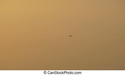 Flying Plane at Sunset - Small plane is turning right on the...