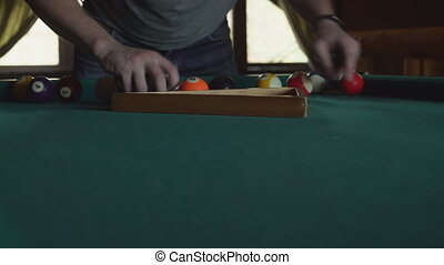 A man puts balls in a triangle for an American billiard,...