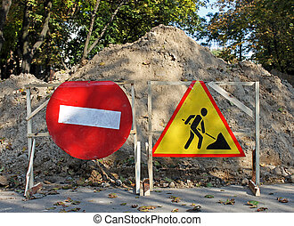 road works sign before heap of ground on a road