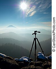 Professional tripod without camera on snowy peak ready for...