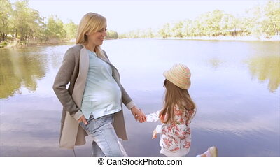 Mom in position with daughter, walk near the lake - Pregnant...