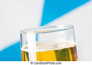 glass full of beer in front of bavarian flag