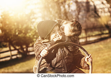 young girl kissing baby on seesaw in warm sunlight
