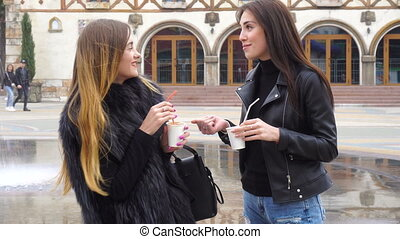 two charming girls drink coffee and talks on the street...