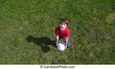 Boy throws up the ball, standing on green field, slow motion