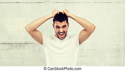 crazy shouting man in t-shirt over gray background -...