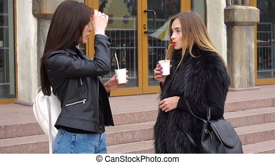 two young girls drinks coffee and talks - two young...