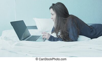 Happy young woman in bed behind laptop. A beautiful girl in blue pajamas lies in a white bed. Work at home on weekends. Morning in bed with laptop.