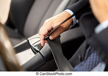 senior businessman fastening car seat belt