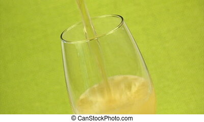Pouring beer in a glass, over a green fabric background