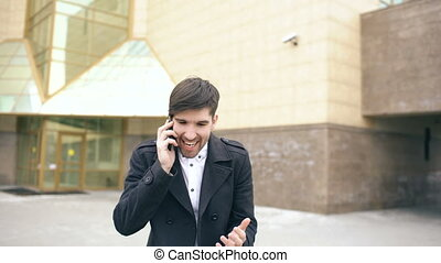 Dolly shot of young business man talking at smartphone and...
